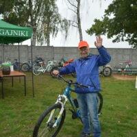 Rowerzysta, uczestnik rajdu stoi przy rowerze zuniesioną ręką.